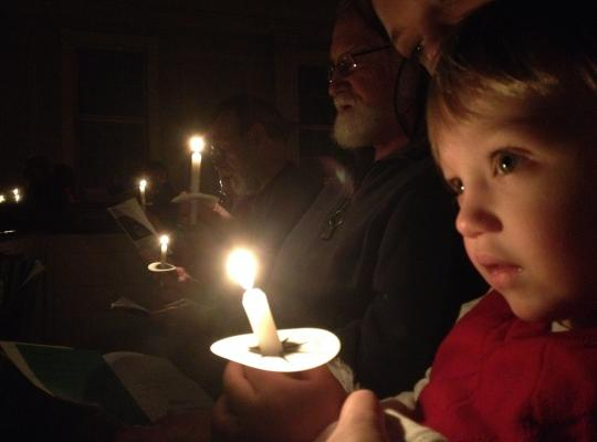 a child holds a candle at the Christmas Eve service